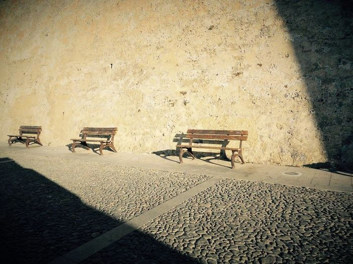 Sardinia Alghero benches Relaxing solitude Port light and shadow Carpe Diem the wall