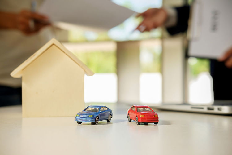 Close-Up Of Toy Cars And Model Home On Table Against Client And Salesman With Documents