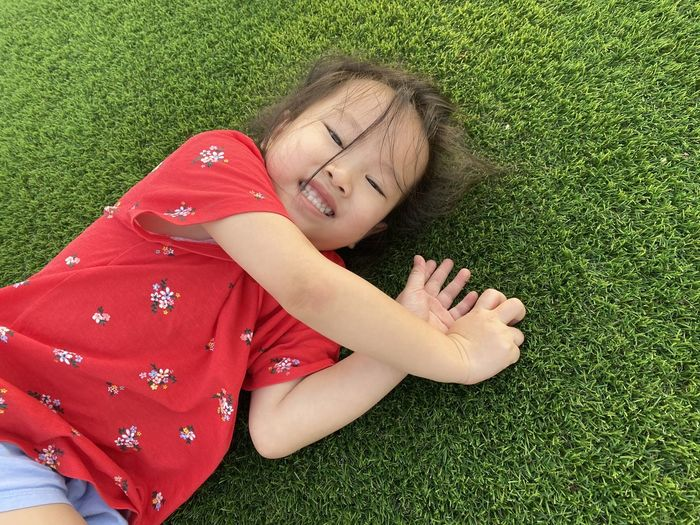 High angle portrait of smiling girl lying on grass