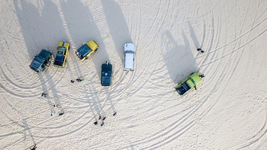 High angle view of people by jeeps at desert