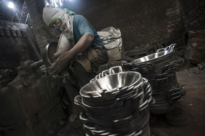 Worker cleaning containers in factory