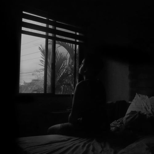 Rear view of woman sitting on bed at home