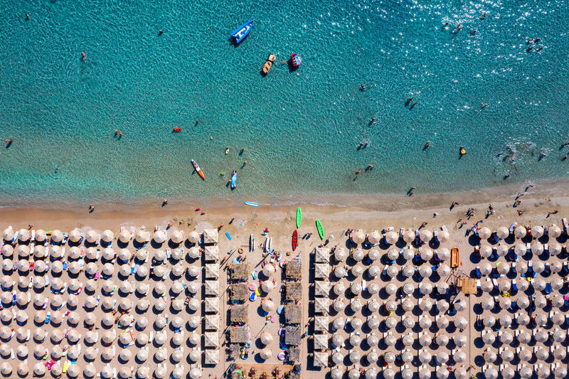 Aerial view of people and beach umbrellas by sea