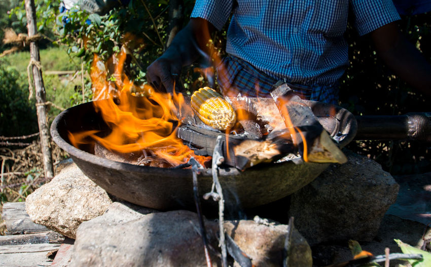 Midsection Of Man Cooking Corn On Fire Pit