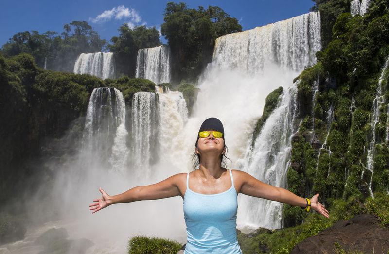 Full length of man standing against waterfall