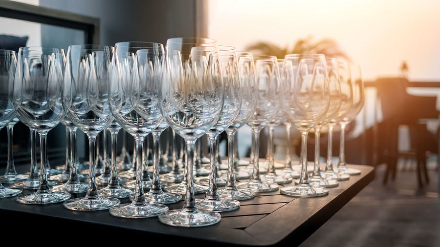 Close-up of wineglasses on table against sky during sunset
