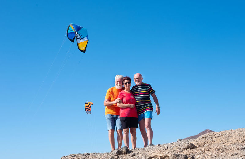 Low angle portrait of happy friends standing at beach against clear sky