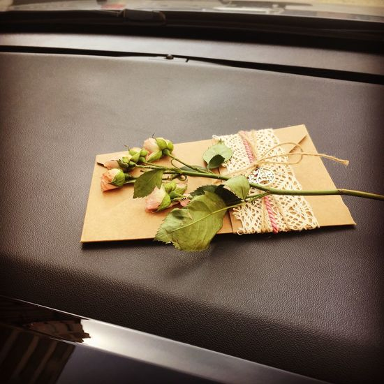 Close-up of flowers and envelop on seat