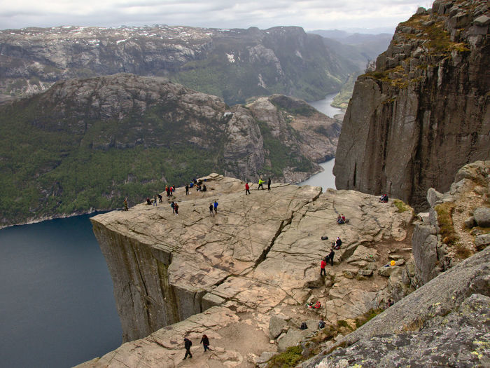 High Angle View Of People Standing On Cliff Against Mountains