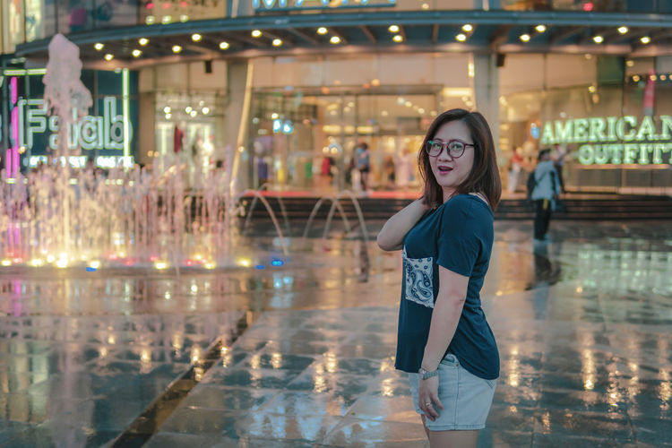 Portrait Of Woman Standing On Footpath Against Illuminated Shopping Mall At Dusk