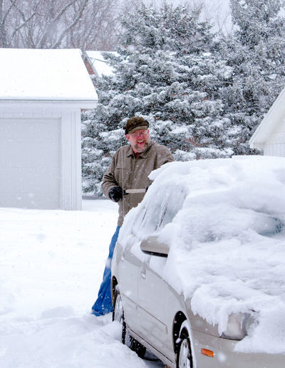 An older man shovels snow off his car after a snow storm in Michigan USA Cars Michigan USA Adult Car Clothing Cold Temperature Day Extreme Weather Full Length Land Vehicle Mode Of Transportation Motor Vehicle One Person Outdoors Senior Adult Shoveling Snow Snow Snowing Standing Transportation Warm Clothing White Color Winter Wintry Scene