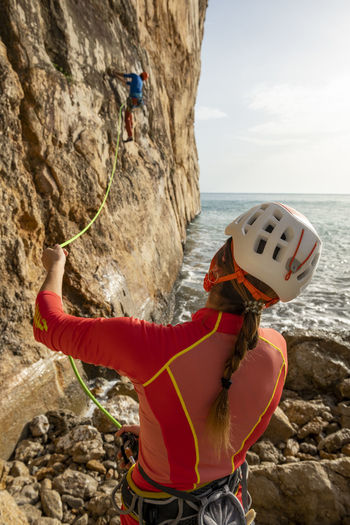 Midsection of person on rock at sea shore against sky