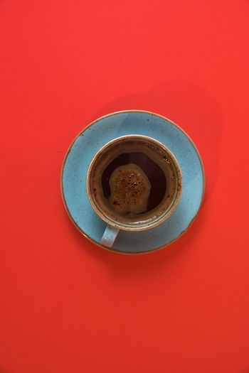 Directly above shot of coffee cup against red background