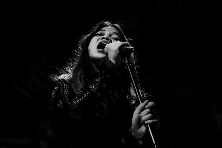 Young woman singing while holding microphone in darkroom