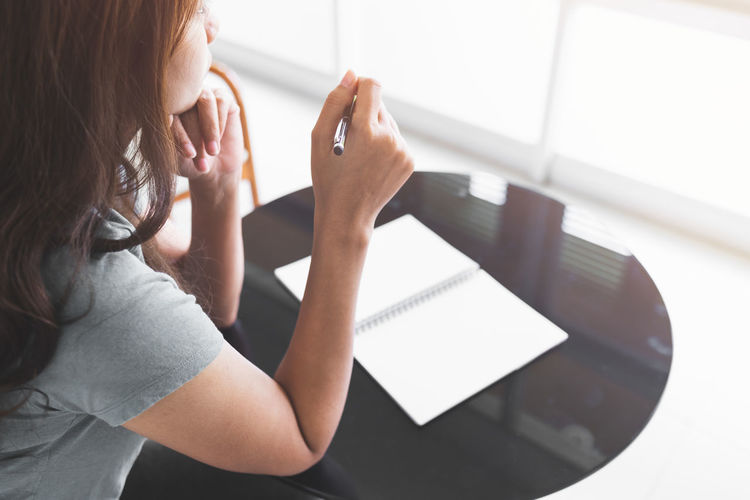 Portrait of woman using mobile phone while sitting on table