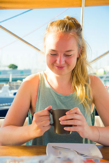 Close-up of young woman drinking coffee while sitting indoors