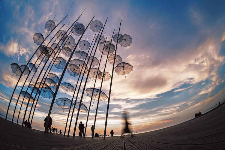 Low angle view of people enjoying at sunset