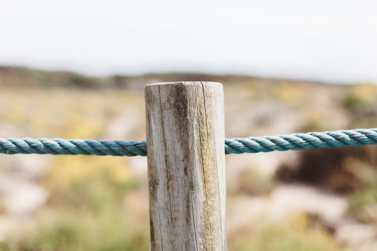 Close-Up Of Wooden Post By Rope Against Sky