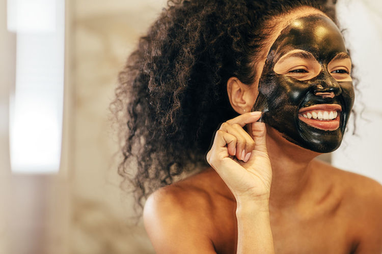 Real People Lifestyles Indoors  Young Adult Curly Hair Black Face Mask Applying Standing Bathroom Mirror Reflection Smiling Happy Towel Spa Treatment Looking Young Females Hygiene Facial One Person Portrait Copy Space