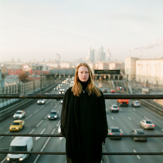 Portrait of young woman standing on bridge in city against sky