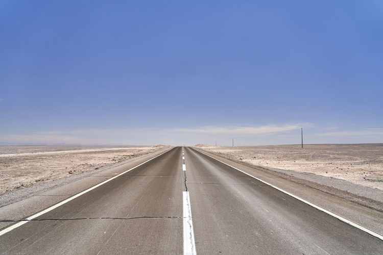 Dark, black tarmac road to nowhere leading straight to the horizon in the atacama desert of chile.