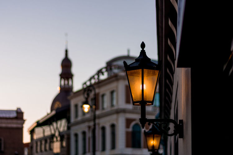 Low angle view of illuminated street light against buildings and sky