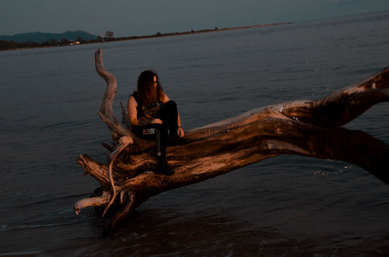 Full length of woman on driftwood at beach against sky