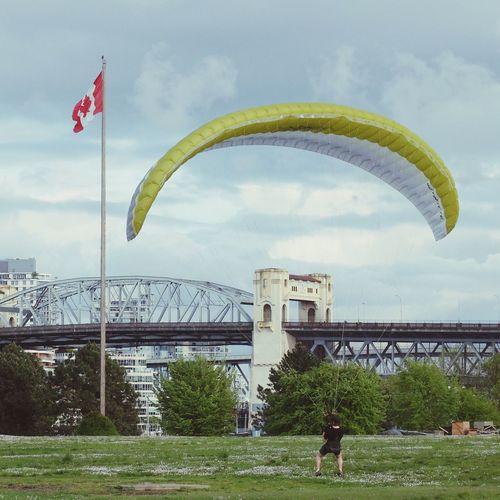 Man landing with parachute against burrard bridge at vanier park
