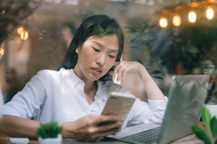 Businesswoman using phone and laptop at table seen through window