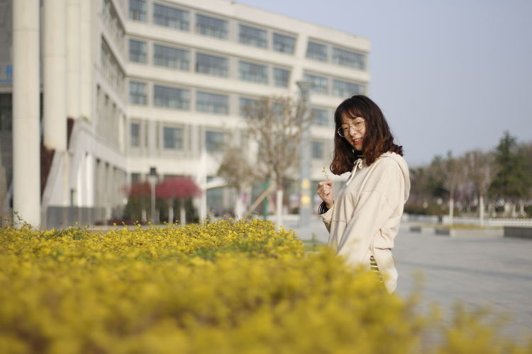 Portrait of smiling young woman standing by plants against building