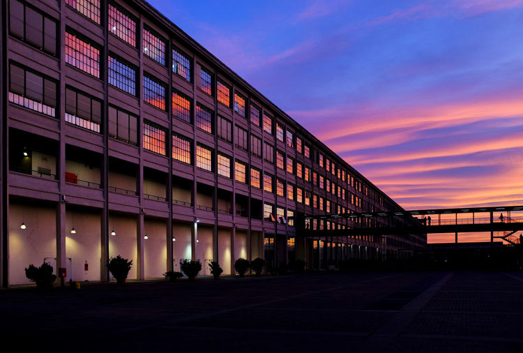 A spectacular sunset reflects on the large windows of a former industrial building Built Structure Architecture Sunset Building Exterior Sky Orange Color Illuminated City Building Glass - Material Outdoors Dusk Silhouette Business Incidental People Cloud - Sky Reflection Twilight Evening Space For Text Space For Copy Copy Space Colorful Industrial Urban Footbridge Evening Sky Façade Windows