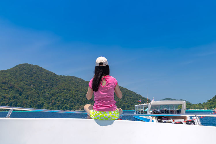 Rear view of woman on mountain against blue sky