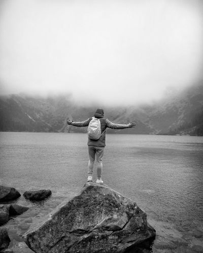 Rear view of man standing on rock by lake