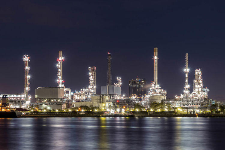 Oil refinery at night petrochemical and energy industry with refection on river
