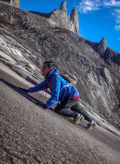 Tilt Shot Of Man Climbing Mountain
