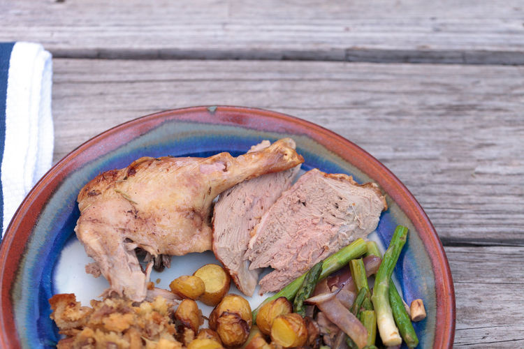 Close-up of roast chicken with vegetables served in plate on wooden table