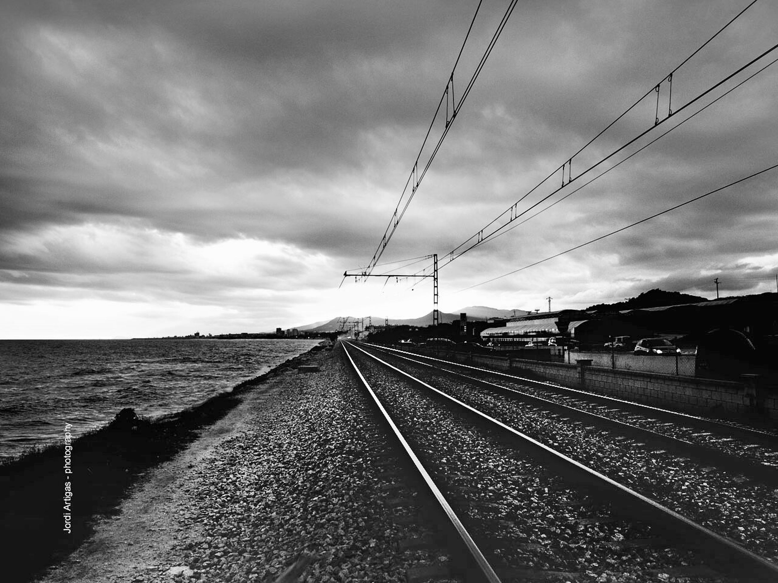 sky, cloud - sky, railroad track, transportation, water, the way forward, cloudy, rail transportation, diminishing perspective, cloud, built structure, vanishing point, architecture, connection, sea, overcast, public transportation, travel, day, outdoors