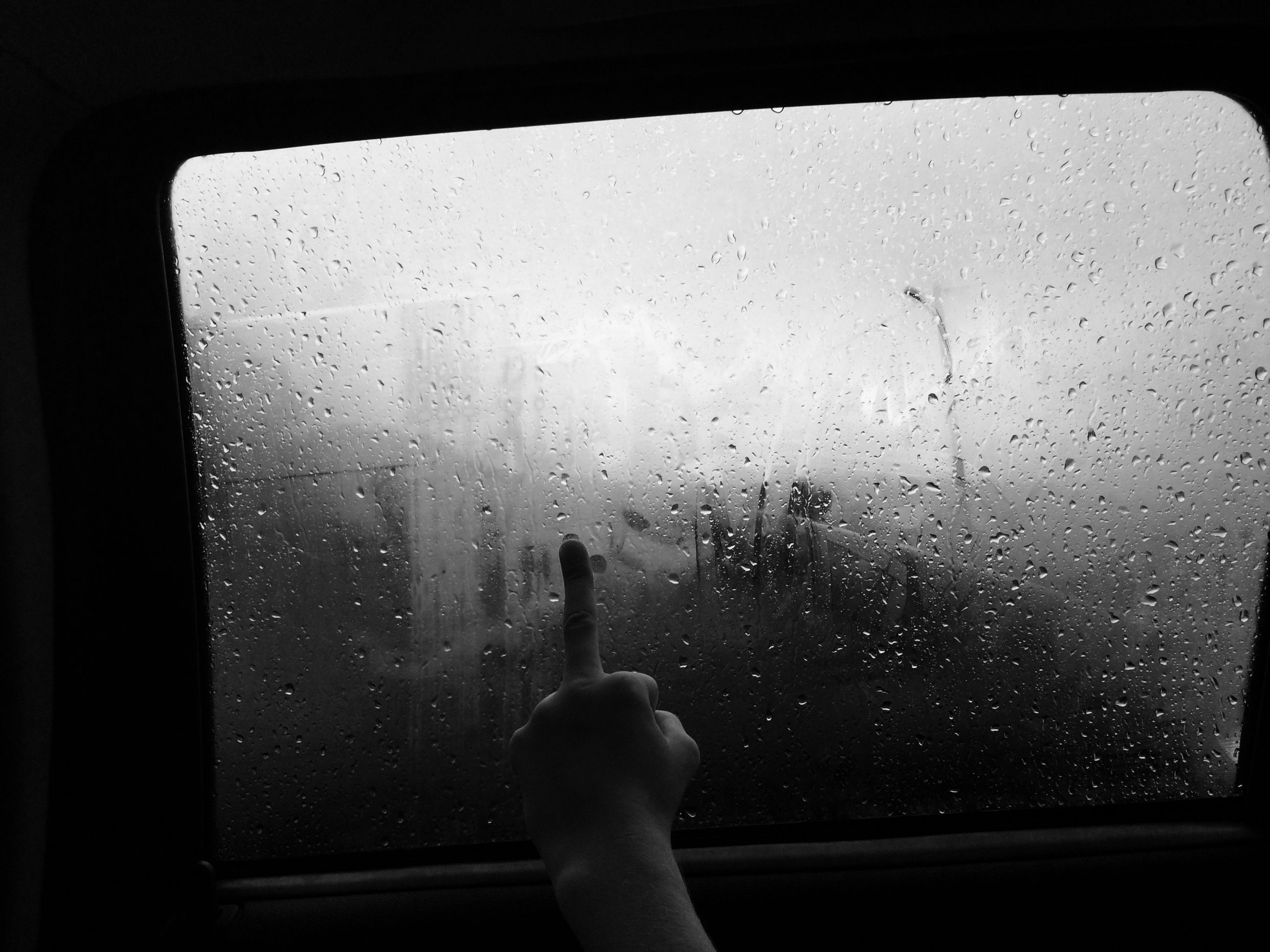 window, indoors, transparent, glass - material, looking through window, vehicle interior, person, lifestyles, glass, wet, drop, part of, water, rain, leisure activity, unrecognizable person, personal perspective