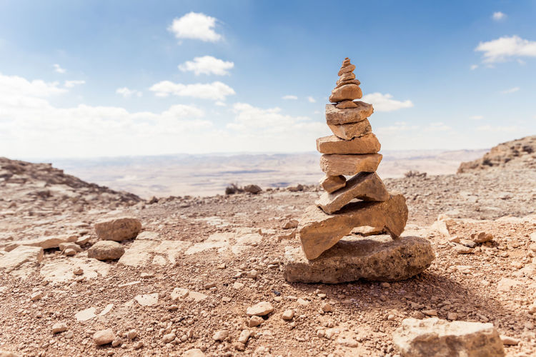 Several small stones placed one on another standing in a park of stones in the Judean Desert near the city of Mitzpe Ramon in Israel Beautiful Nature Chaotically Heavy Nature Rock Skyline Standing View Background Blue Sky Cliff Cloud - Sky Day Hill Israel Judean Desert Landmark Landscape Large Stones Mitzpe Ramon Mountain Park Of Stones Scenics - Nature Tourism Destination Tranquil Scene