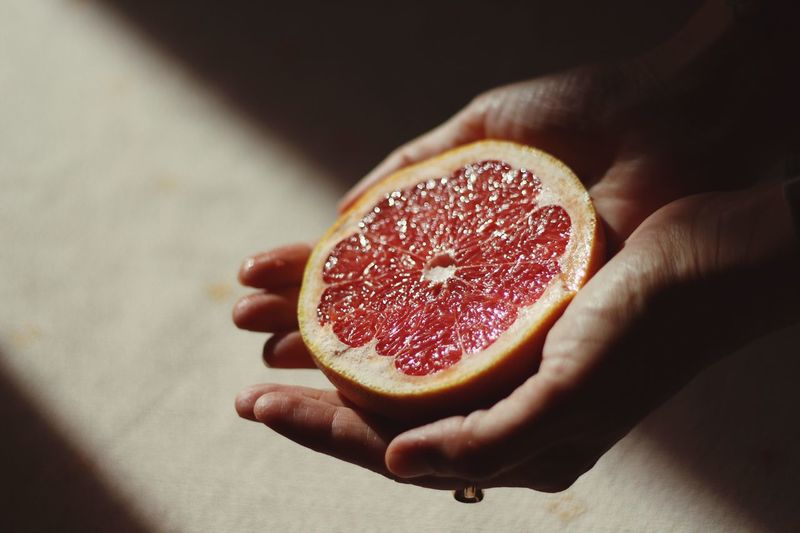 Cropped image of person holding halved grapefruit in sunlight