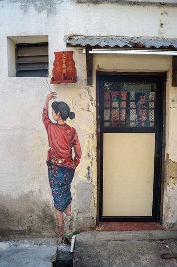 Rear view of woman standing against door of building