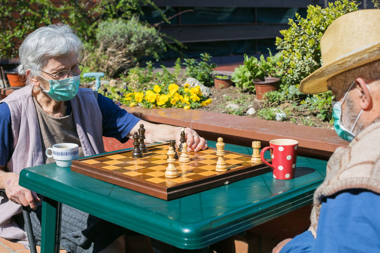 Senior couple playing chess on table while sitting outdoors