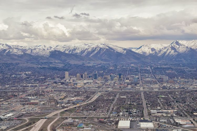 Downtown Salt Lake City Panoramic view of Wasatch Front Rocky Mountains from airplane in early spring winter with melting snow and cloudscape. Utah, USA. Cloud - Sky Architecture City Sky Cityscape Built Structure Building Exterior Nature Mountain Outdoors Snowcapped Mountain Mormon Mormon Life Mormon Temple Lds LDS Temple Brigham Young Wasatch Mountains Rocky Mountains Urban City Panorama Banner Drone  Airplane Aerial View Aerial
