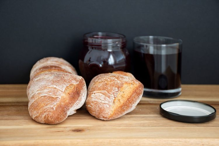 Table Food And Drink Indoors  Food Still Life Bread Wood - Material Freshness Jar Close-up No People Glass - Material Drink Ready-to-eat Focus On Foreground Black Background Breakfast Glass Blueberry Jam Jam Baked Wooden