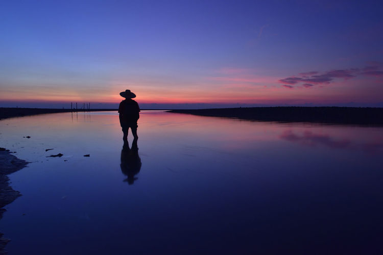 Silhouette man standing in shallow water at beach against sky during sunset