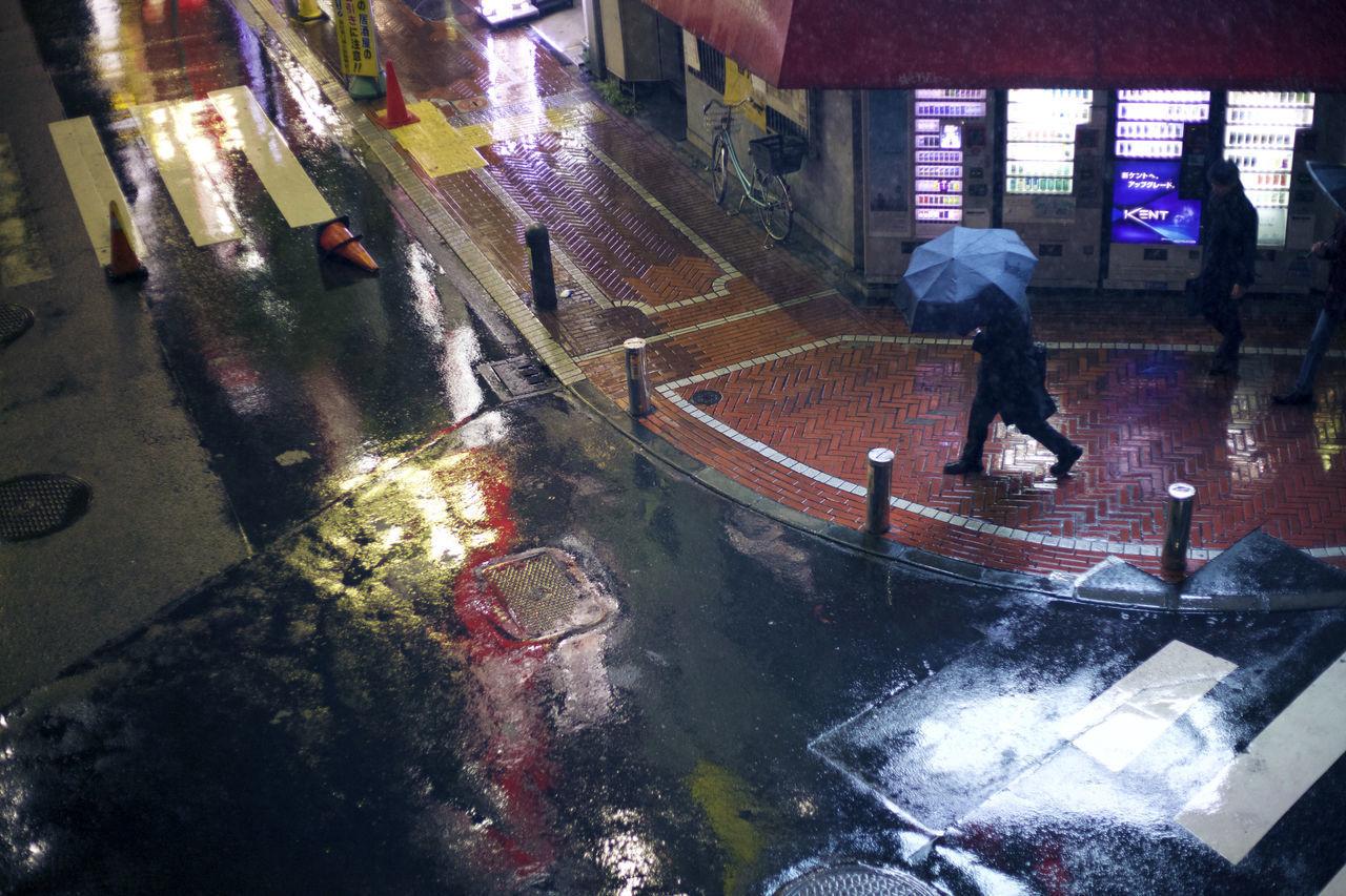 REAR VIEW OF MAN WALKING ON WET STREET AT NIGHT