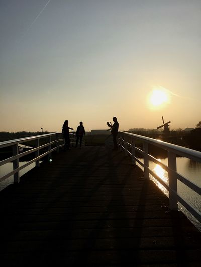 Railing Sunset Sky Real People Leisure Activity Lifestyles Walking Sunlight Men Silhouette Outdoors The Way Forward Women Standing Bridge - Man Made Structure City Sun Togetherness Staircase Day