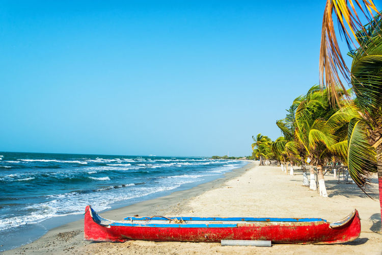 White sand Caribbean beach with a red canoe in the foreground Beach Blue Boat Canoe Caribbean Coast Colombia Coveñas Forest Idyllic Landscape National Park Nature Ocean Palm Rock Sand Santa Marta Sea Table Tolu Travel Trees Tropical Water