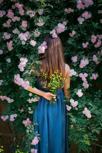 Low section of woman standing by pink flowering plants