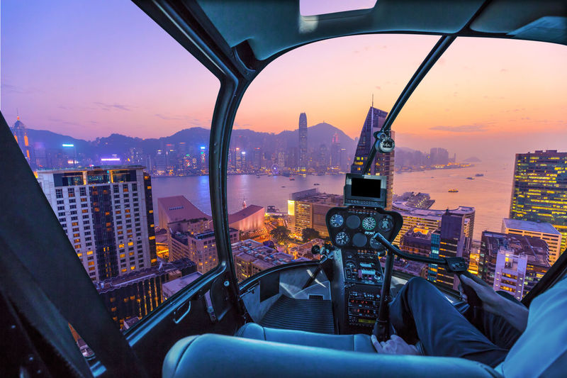 Illuminated cityscape against sky during sunset seen through helicopter